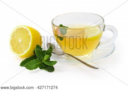 Glass Cup Of The Tea With Mint Leaf And Lemon Slice On The Glass Saucer With Tea Spoon, Twig Of Fres