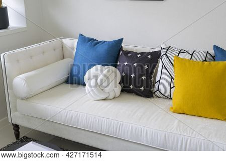 Modern Living Room With Blue, White And Yellow Pillow On Sofa. Coffee Table With Plant Pot And Gold