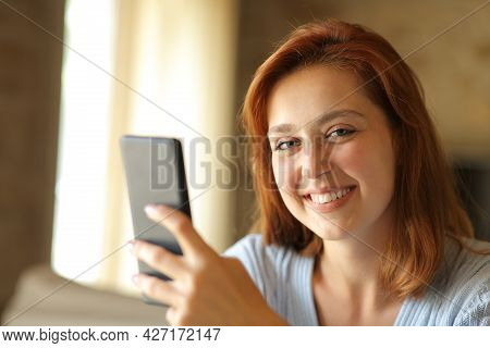 Happy Woman Holding Smart Phone Looks At Camera Sitting At Home