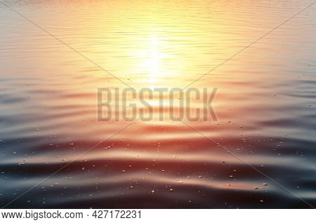 Close-up Of The Sunset At The Sea. Calm Surface Of Dark Blue Water And Yellow-red Reflex From The Su