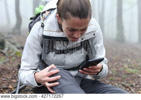 Injured Trekker Checking Smart Phone Asking For Help In The Mountain A Foggy Day