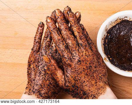 Female Hands With Coffee Scrub And A Cup With Coffee Scrub On The Table, Top View