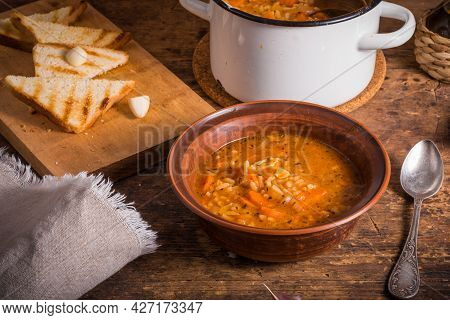 Rustic Vegetarian Rice Soup With Tomato And Carrot In A Clay Bowl And Triangular Garlic Toast