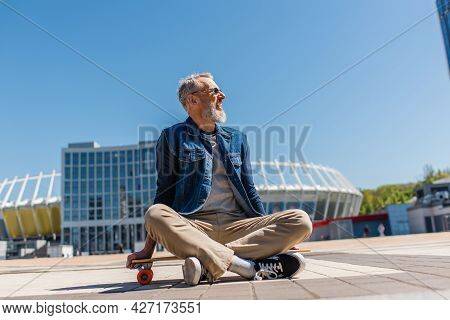 Pleased Middle Aged Man In Sunglasses Sitting On Longboard Outside