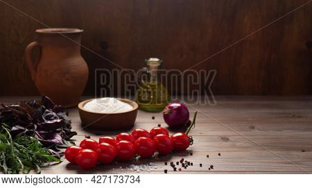 Food ingredients for pizza cooking and tomato with spice for homemade bread baking on table. Spice and herb at wooden tabletop background. Bakery concept in kitchen