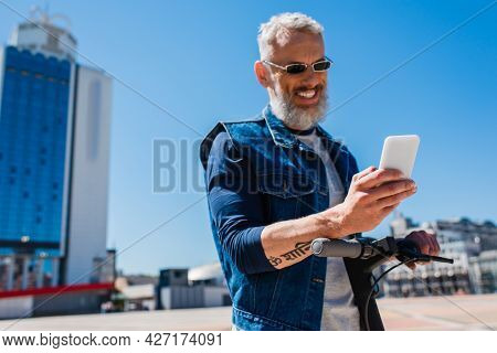 Cheerful And Mature Man Using Smartphone Near E-scooter Outside