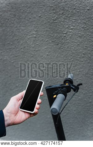 Partial View Of Mature Businessman Holding Smartphone With Blank Screen Near E-scooter
