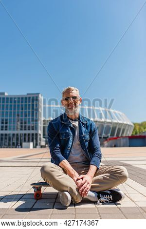 Positive Middle Aged Man In Sunglasses Sitting On Longboard Outside