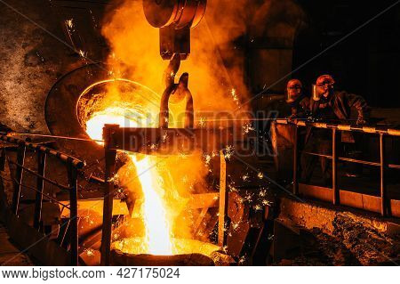 Iron Casting. Molten Metal Pouring From Blast Furnace Into Ladle. Steel Production In Foundry Worksh
