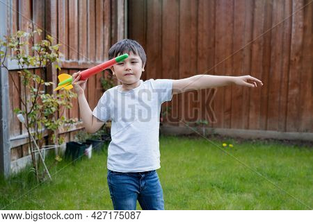 Active Kid Preparing To Throwing A Javelin, Healhty Child Practicing Athletics Throw Javelin. Outdoo