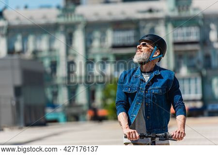 Positive Man In Sunglasses And Helmet Riding E-scooter In Urban City