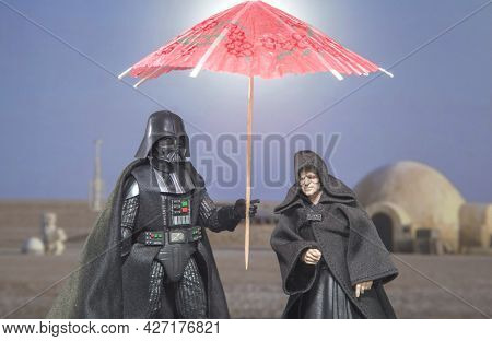 JUNE 12 2021: Humor image, Star Wars Sith Lord Darth Vader and Emperor Palpatine on Tatooine with sun umbrella - Hasbro action figure