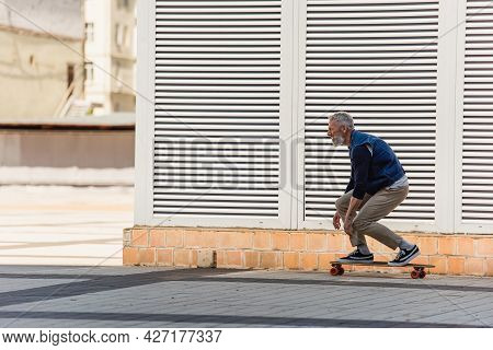 Side View Of Positive And Middle Aged Man Riding Longboard On Urban Street