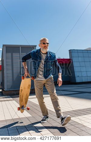 Focused Middle Aged Man In Sunglasses Holding Longboard On Urban Street