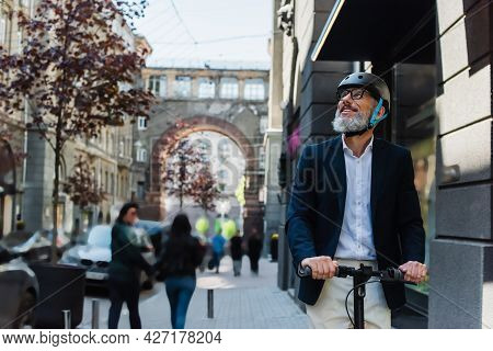 Mature Businessman In Blazer And Helmet Riding E-scooter And Looking Away Outside