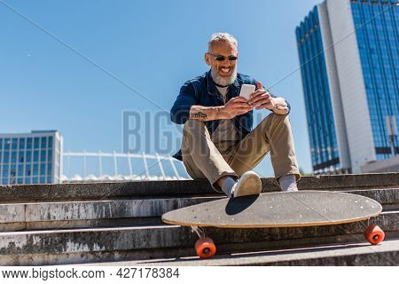 Happy Middle Aged Man In Sunglasses Sitting On Stairs Near Longboard While Using Cellphone On Urban