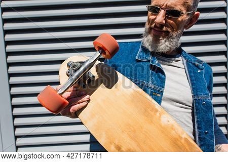 Smiling And Middle Aged Man In Sunglasses Holding Longboard