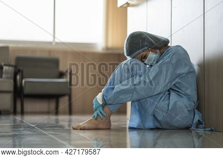 Asian Woman Doctor Wearing Surgical Face Mask Sitting On Thr Floor Tired From Work Because Impact Fr