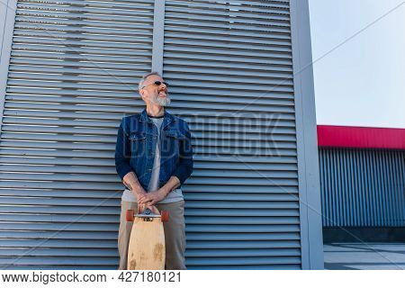 Happy Middle Aged Man In Sunglasses Holding Longboard And Looking Up On Urban Street