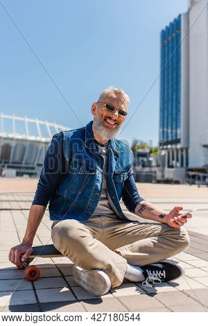 Cheerful Middle Aged Man In Sunglasses Sitting On Longboard While Using Cellphone On Urban Street