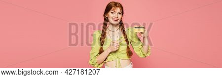 Smiling Woman With Freckles Pointing At Credit Card Isolated On Pink, Banner