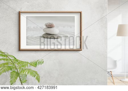 Wooden picture frame with zen stones photo on the wall interior concept