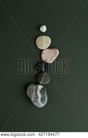 Zen stones stacked on green background in health and wellbeing concept