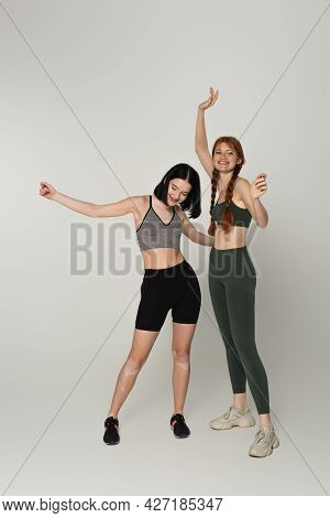 Cheerful Young Sportswomen With Vitiligo And Freckles Dancing Together On Grey Background