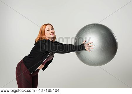 Plus Size Sportswoman Holding Fitness Ball And Looking At Camera Isolated On Grey