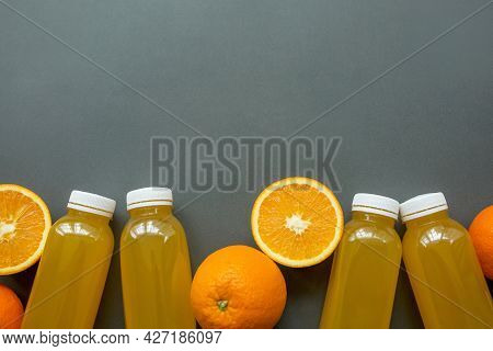Bottles Of Freshly Squeezed Orange Juice And Oranges On A Gray Background. The Concept Of A Healthy