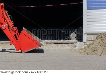 Repair On The Territory Of The Production Base. A Red Bucket Of A Bulldozer Or Excavator And A Pile