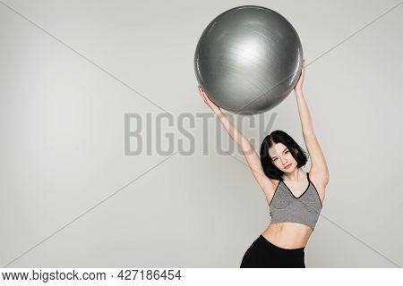 Brunette Sportswoman With Vitiligo Holding Fitness Ball Isolated On Grey