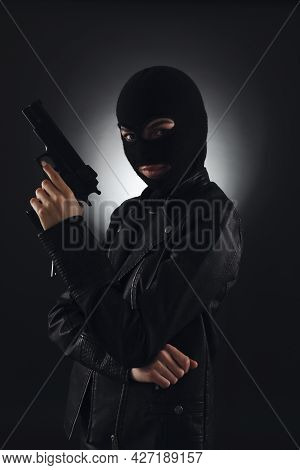 Woman Wearing Knitted Balaclava With Gun On Black Background