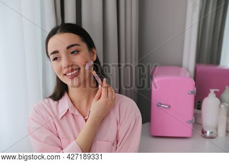 Woman Doing Face Massage At Dressing Table With Cosmetic Refrigerator Indoors