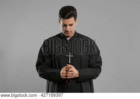 Priest With Rosary Beads Praying On Grey Background