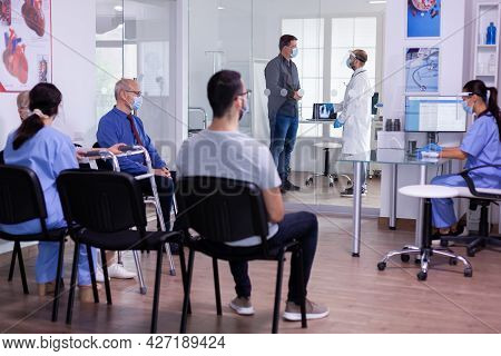 Crowded Hospital Waiting Room With Patients Sitting On Chairs Respecting Social Distencing And Nurse