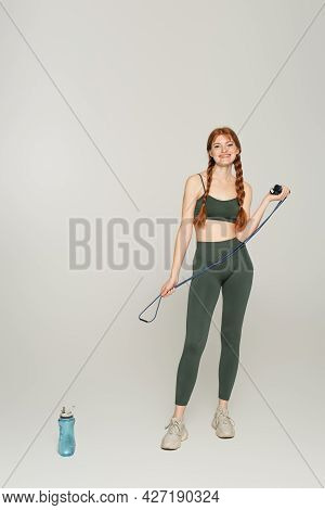 Cheerful Sportswoman With Freckles Holding Jump Rope Near Sports Bottle On Grey Background