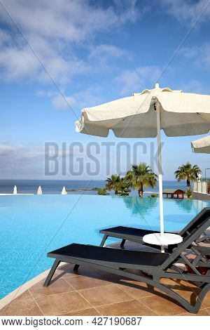 Chaise Longues And Beach Parasol Near Infinity Pool At Resort