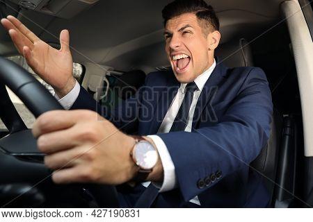 Emotional Man Yelling In Car. Aggressive Driving Behavior