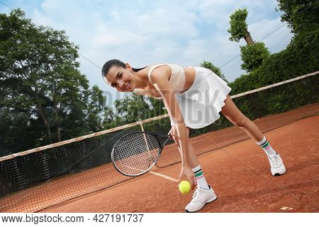 Professional Sportswoman With Tennis Racket And Ball At Court