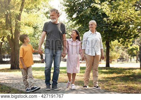 Happy Grandparents With Little Children Walking Together In Park