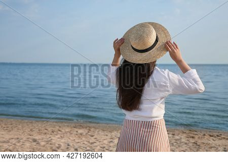 Beautiful Young Woman Wearing Straw Hat On Beach, Back View. Stylish Headdress