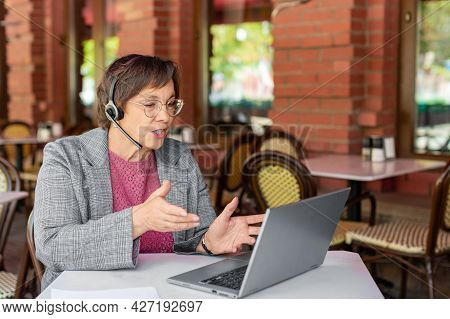 Senior Woman Is Online Working In Front Of Laptop Monitor.