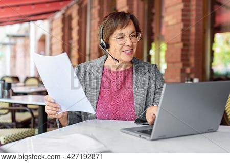 Senior Woman With Headset Is Filling Forms Whie Sitting In Front Of Laptop Monitor At Summer Cafe.