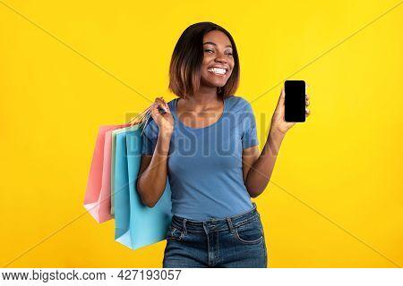African Woman Showing Smartphone Screen Posing With Shopper Bags, Studio