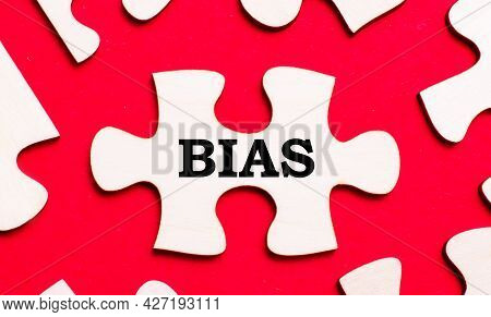 On A Bright Red Background, White Puzzles. In One Of The Pieces Of The Puzzle, The Text Bias