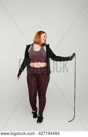Side View Of Smiling Body Positive Sportswoman Holding Jump Rope On Grey Background