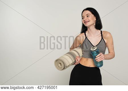 Smiling Sportswoman With Vitiligo Holding Fitness Mat And Sports Bottle Isolated On Grey