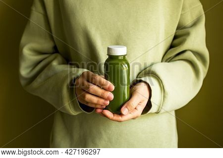 A Woman In A Green Sweater Is Holding A Bottle Of Freshly Squeezed Green Juice Or A Smoothie. The Co