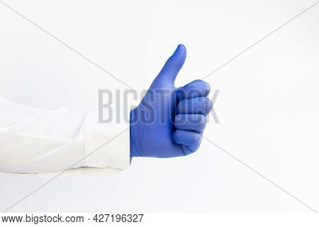 Doctor Wearing Blue Latex Glove Giving Thumbs Up Sign. White Background. Copy Space